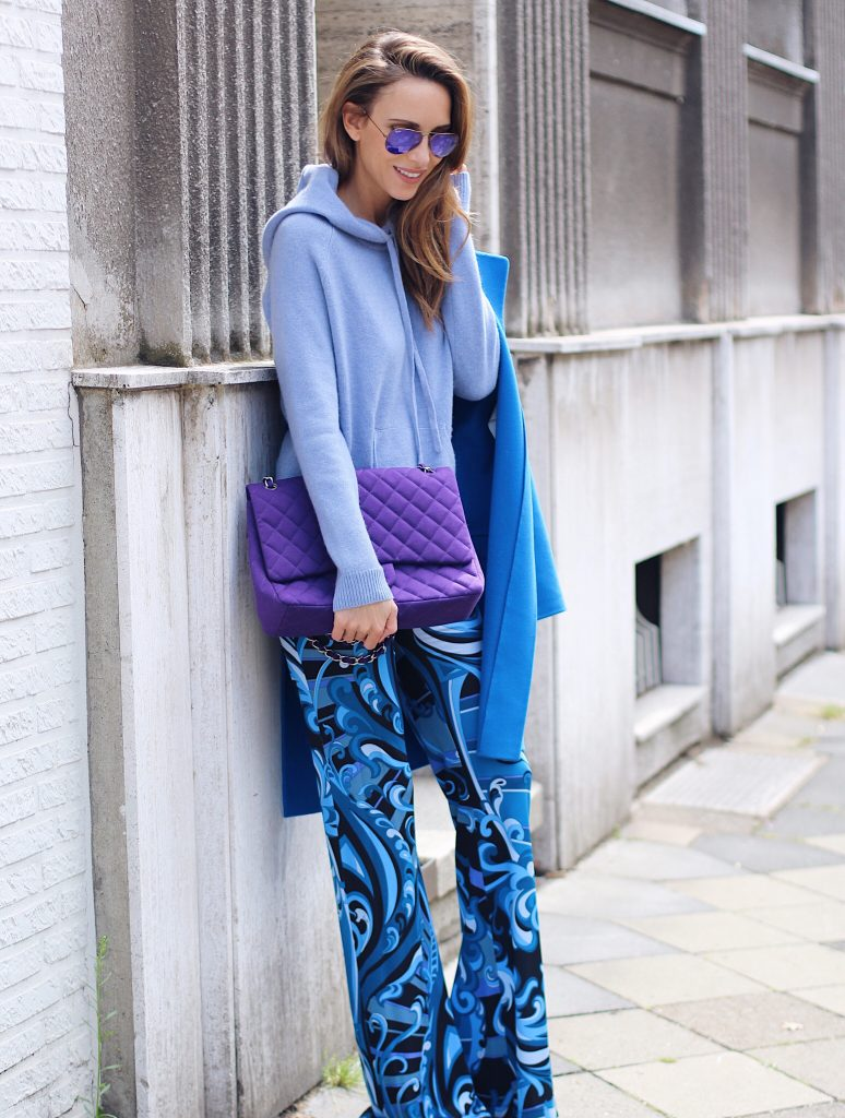 Alexandra Lapp wearing a light blue cashmere hoodie by Heartbreaker, colorful pants in all tones of blue from Emilio Pucci, a blue cashmere coat by Jil Sander, an oversized purple 2.55 tweed bag from Chanel, purple aviator sunglasses from Ray Ban, Gianvito Rossi heels.