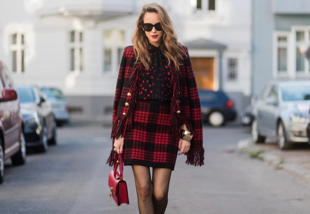 Model and fashion blogger Alexandra Lapp wearing a military jacket in red and black with checkered pattern and frayed sleeves from Balmain, plaid pattern high waist mini skirt by Balmain, red heart intarsia knit by Red Valentino, Celine Box bag in red and red lacquer pumps by Gianvito Rossi, rose gold ring with baguette diamonds on August 4, 2017 in Duesseldorf, Germany.