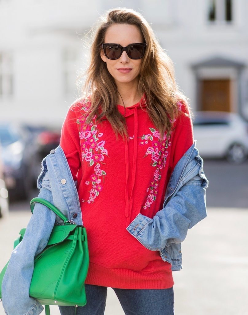 Model and fashion blogger Alexandra Lapp wearing color blocking, oversized denim jacket by SET, high waist denim from Rag and Bone Jeans, red cashmere hoodie with pink flowers by Heartbreaker, green Kelly bag by Hermes, Lolacramp color blocking heels from Christian Louboutin and Gucci sunglasses on August 5, 2017 in Duesseldorf, Germany.