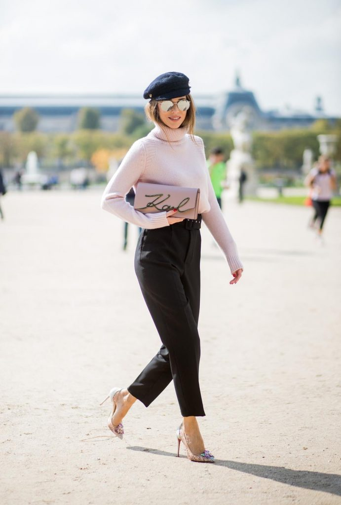 Alexandra Lapp wearing high waist pants in black from Zara, cashmere turtleneck in light pink from Jil Sander, light pink calf leather logo plaque shoulder bag from Karl Lagerfeld, Karl Lagerfeld bag, mirrored sunglasses by Le Specs, hat by Chanel, IWC Portugieser watch and Christian Louboutin Feerica heels with crystal embellished flower and glitter is seen during Paris Fashion Week Spring/Summer 2018 on September 29, 2017 in Paris, France.