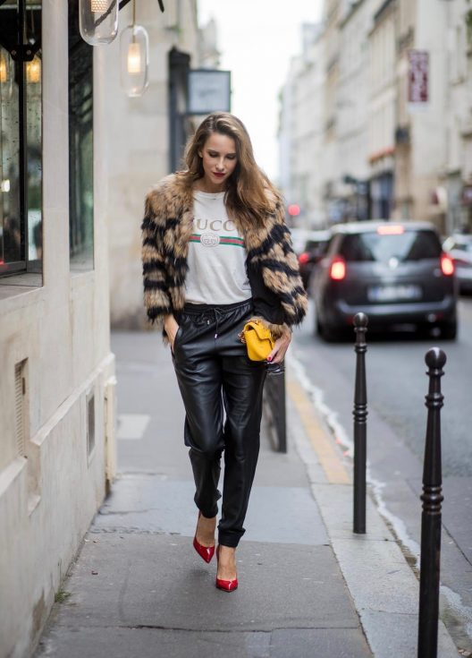 Alexandra Lapp wearing leather trackies in black from Set Fashion, vintage style Gucci logo tee, little fur jacket by Set, yellow GG Marmont matelasse shoulder bag by Gucci, red lacquer heels from Gianvito Rossi and Audrey sunglasses from Celine is seen during Paris Fashion Week Spring/Summer 2018 on September 27, 2017 in Paris, France.