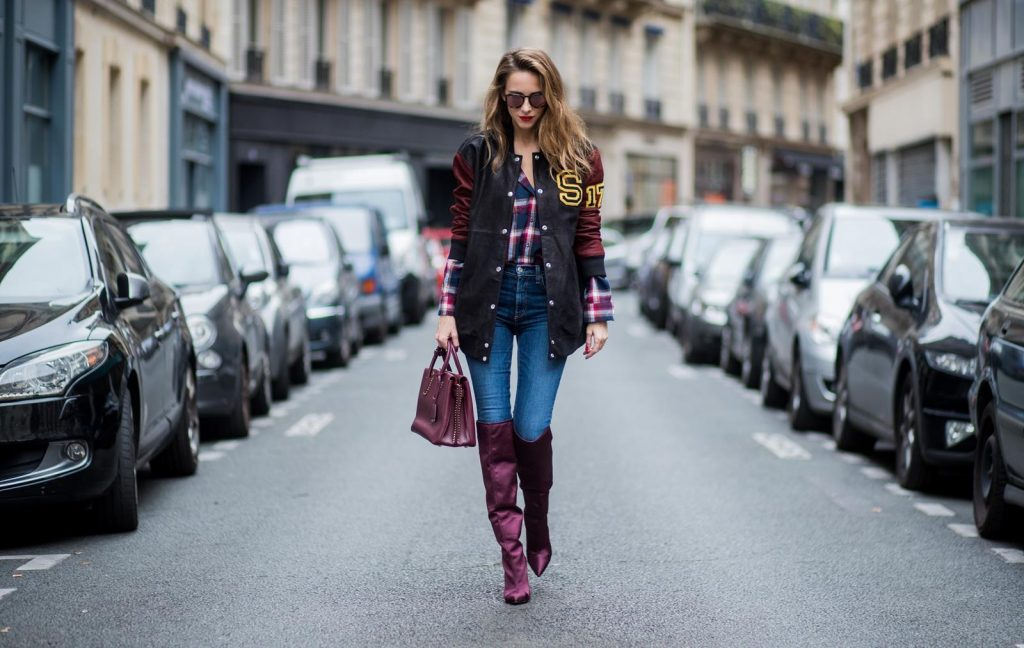 Alexandra Lapp wearing an oversized college jacket in leather from Set Fashion, a plaid shirt with studs from Set, high waist skinny jeans by Rag and Bone, Milla Tote bag with studded outlines in rustic brown from MCM, Les Specs sunglasses, and overknee boots in burgundy by Zara is seen during Paris Fashion Week Spring/Summer 2018 on September 26, 2017 in Paris, France.