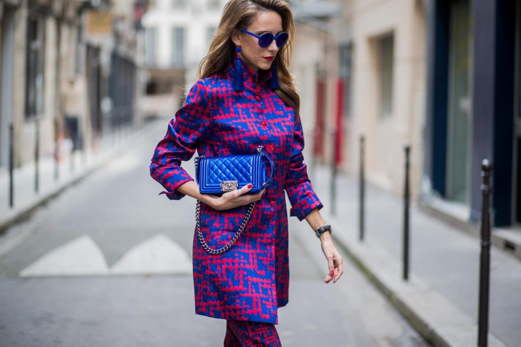 Alexandra Lapp wearing a two-piece suit in red and blue by Riani, a blue lacquer Chanel Boy bag, blue sunglasses by Etnia Barcelona, plexi pumps in blue from Gianvito Rossi and blue tassel earrings from Zara is seen during Paris Fashion Week Spring/Summer 2018 on September 26, 2017 in Paris, France.