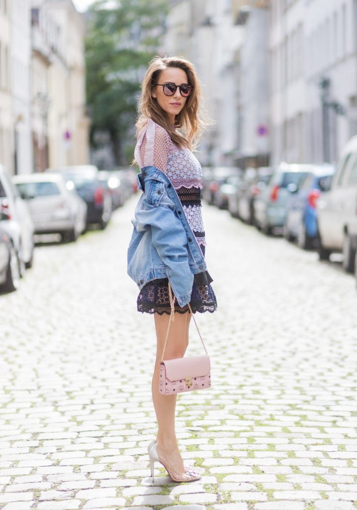 Model and fashion blogger Alexandra Lapp wearing a Self-Portrait dress out of lace in pastel rose, oversized denim jacket from SET, Christian Louboutin Feerica heels with Swarovski crystals and flower accessory, Millie crossbody bag in pink from MCM and sunglasses by Le Specs on August 5, 2017 in Duesseldorf, Germany.