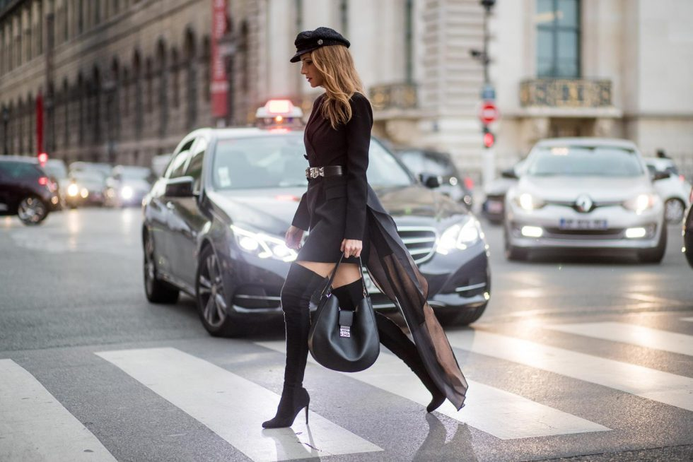 Alexandra Lapp wearing a Tuxedo Dress with detachable overlay in black from Pearl and Rubies, collier de chien waist belt by Hermes, black overknee boots from Gianvito Rossi, hat by Chanel and Patricia Hobo bag with a rounded shape and a Laurel Lock closure seen during Paris Fashion Week Spring/Summer 2018 on October 2, 2017 in Paris, France.