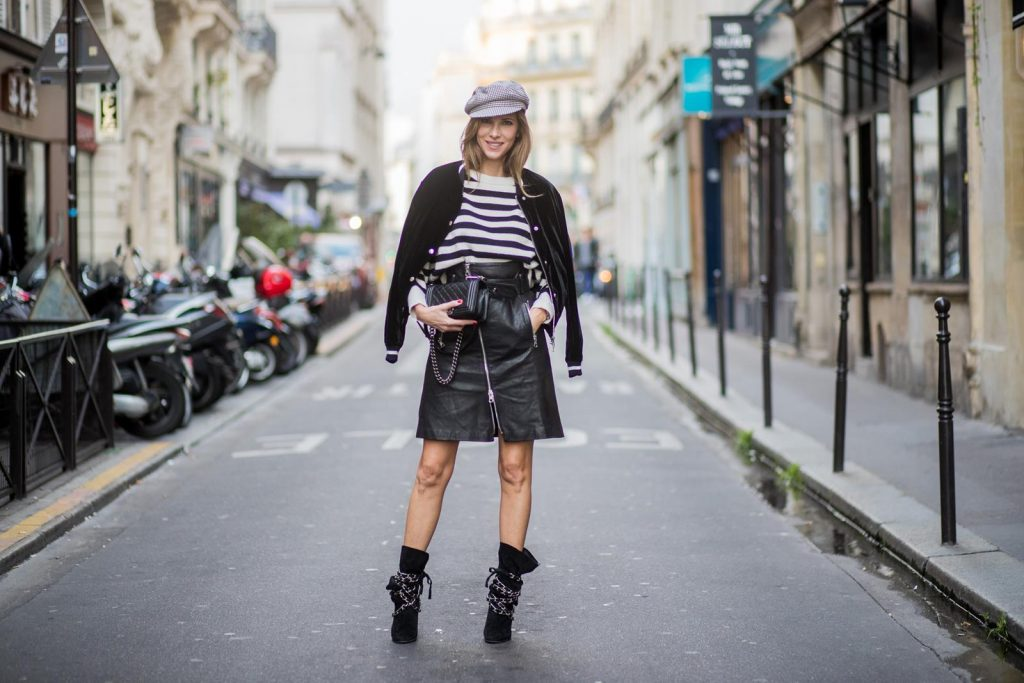 Alexandra Lapp wearing French Chic, an A-line leather rocky biker skirt from SET Fashion, striped knit jumper from Zara, plaid Zara hat, Isabel Marant slouchy boots, detailed with chain-trimmed ties to wrap around the leg, black Boy bag from Chanel and velvet bomber jacked with a Cosmo application is seen during Paris Fashion Week Spring/Summer 2018 on September 29, 2017 in Paris, France.
