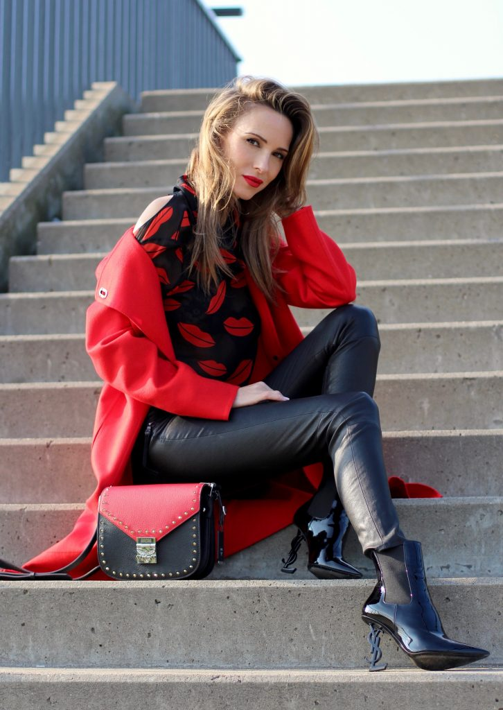 Alexandra Lapp wearing the new MCM Made-To-Order Patricia bag, a Made-To-Order service, giving everyone the opportunity of designing her own personal and unique Patricia bag, black leather pants from Unravel, a silk blouse with red lips from Saint Laurent, a cashmere coat in red from Hermès, black patent ankle boots from YSL, red lipstick by Dior.