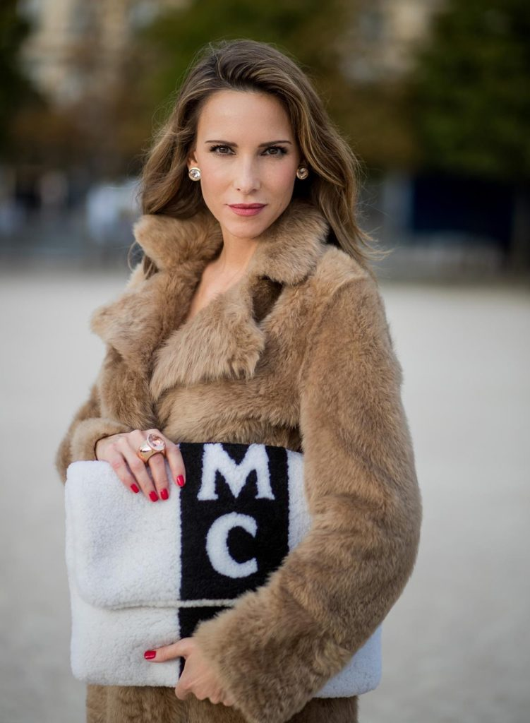 Alexandra Lapp wearing Morganite jewelry, rings and earrings by Schubart an oversized MCM Stark Pouch in Shearling Stripe, a lambskin coat in light brown by Yves Salomon, black and white big waist-belt from Balmain and striped Christian Louboutin 'So Kate' heels is seen during Paris Fashion Week Spring/Summer 2018 on September 28, 2017 in Paris, France.