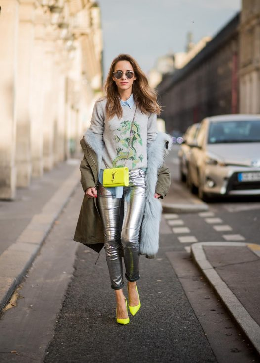 Alexandra Lapp wearing silver pants in leather and biker style by Balmain, long blue silk blouse from Equipment, cashmere pullover in grey with a green dragon application by Heartbreaker, green parka equipped with light blue fur inside, silver mirrored sunglasses by le Specs, Christian Louboutin So Kate heels in neon yellow and the Kate Monogram Chain Grain leather shoulder bag in neon yellow by Saint Laurent is seen during Paris Fashion Week Spring/Summer 2018