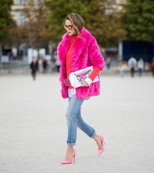 Alexandra Lapp wearing a fake fur jacket in pink from Jakke with a Faux Real statement on the back, red cashmere jumper by Heartbreaker with golden buttons, a long white blouse by Celine, Levis ReDone denim, Christian Louboutin heels in neon pink, sunglasses by Le Specs and a clutch by Yazburkey with a Dazzlin Smile application is seen during Paris Fashion Week Spring/Summer 2018 on September 27, 2017 in Paris, France.
