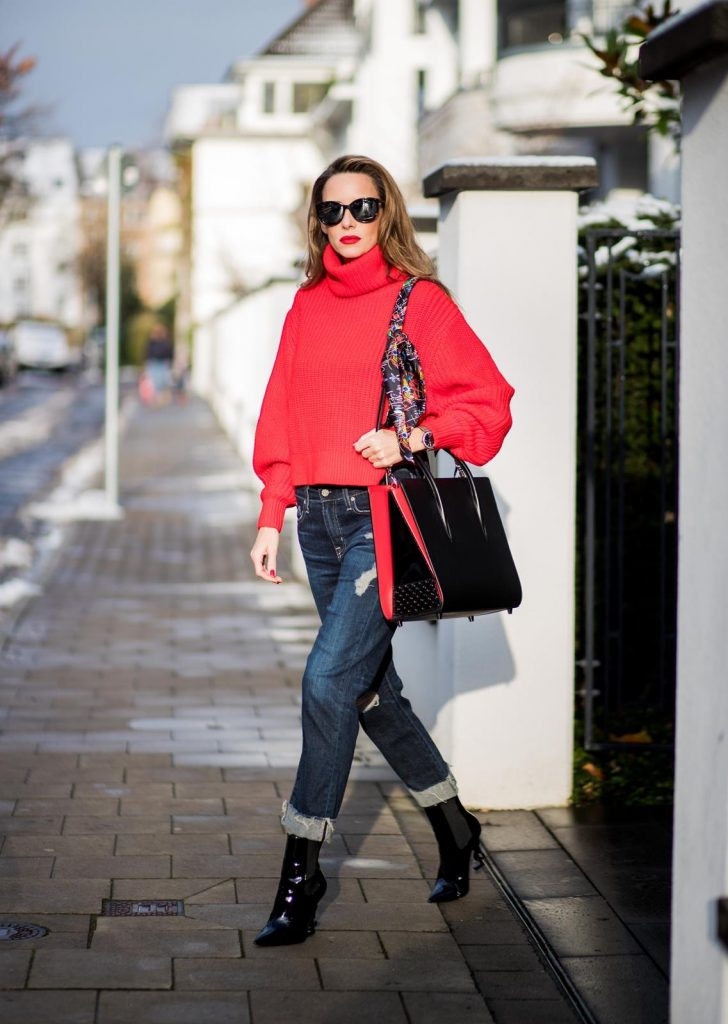 Alexandra Lapp wearing a cropped red turtleneck from H&M, Adriano Goldschmied Boyfriend denim from AG Jeans, Diormania sunglasses by Dior, Opyum 110 ankle boots in patent from Dior, Paloma medium handbag from Christian Louboutin, IWC watch on December 11, 2017 in Duesseldorf, Germany.