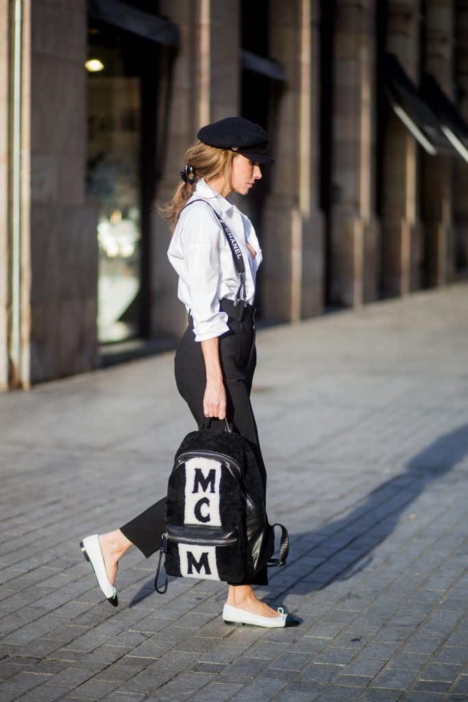 Alexandra Lapp wearing black and white vintage Chanel suspenders with Chanel logo in black and white, a white oversized shirt from Steffen Schraut, black high waist pants from Zara, XL backpack in lambskin with black and white MCM logo and Chanel baker boy cap in black tweed and ballerinas in white with black tip and logo from Chanel on November 27, 2017 in Barcelona, Spain.