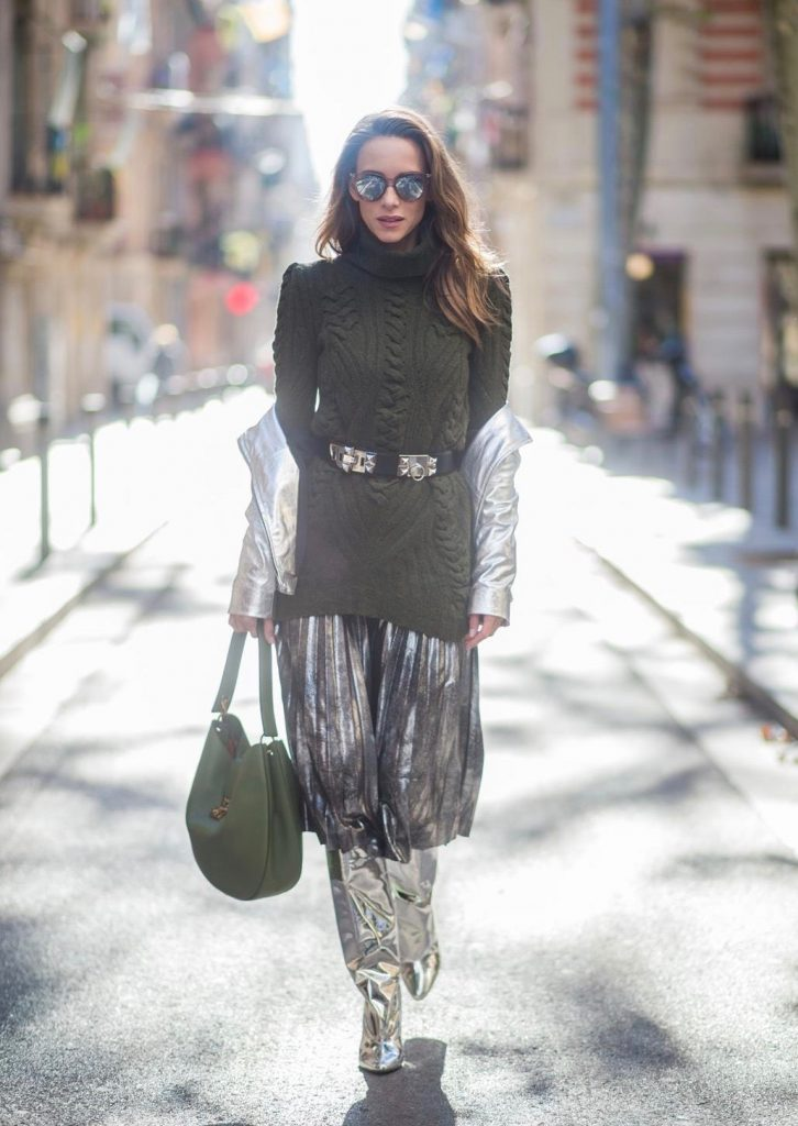Alexandra Lapp wearing metallic look, a pleated skirt in a washed out silver metallic and black style, long knitted dark green Celine turtle neck pullover with cable stitch, black waist belt from Hermes with heavy silver buckle and silver stud details, short cut silver leather jacket with zippers from Set Fashion, silver metallic boots from H&M, large green Patricia Hobo bag from MCM and sunglasses from Le Specs on November 28, 2017 in Barcelona, Spain.