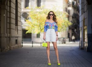 Alexandra Lapp wearing a flower look, blue cashmere cardigan with stitched flower applications from Heartbreaker of shoulder style, white leather skirt with silver buckles in front from Manokhi, neon yellow monogram bag from Yves Saint Laurent with silver chain and buckle, neon yellow So Kate pumps from Christian Louboutin and Audrey sunglasses from Celine on November 29, 2017 in Barcelona, Spain.