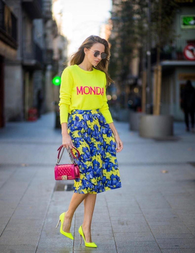 Alexandra Lapp wearing the yellow Alberta Ferretti Monday jumper, pleated skirt with flower prints by Balenciaga, a dark red quilted small boy bag by Chanel, neon yellow pumps by Christian Louboutin and silver Ray Ban sunglasses on November 29, 2017 in Barcelona, Spain.