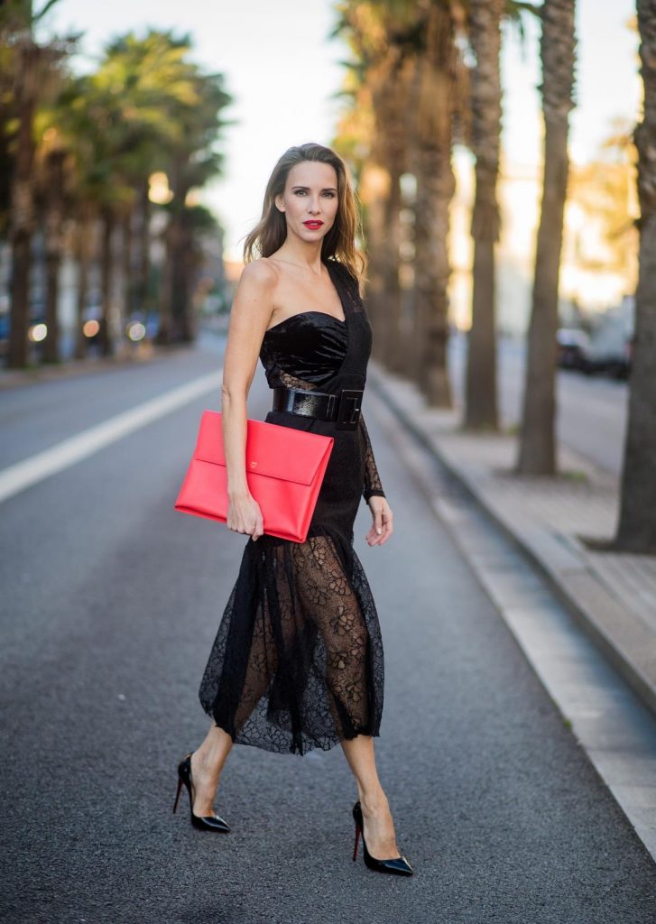Alexandra Lapp wearing a little black dress, asymmetric shoulder dress with a delicate floral lace and a velvet fitted bustier from Three Floor, Pigalle Christian Louboutin black patent leather heels and a simple MCM pouch in marigold orange on November 29, 2017 in Barcelona, Spain.