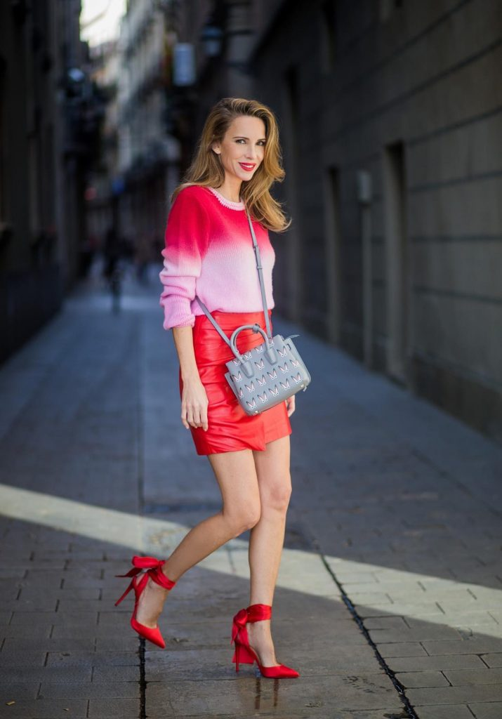 Alexandra Lapp wearing batik knit, a red leather mini skirt with integrated belt around the waist from Set Fashion, a batik cashmere pullover in pink and red from Heartbreaker, red satin pumps from Christian Louboutin with long satin bow, silver shadow colored MCM Milla Tote bag on November 27, 2017 in Barcelona, Spain.