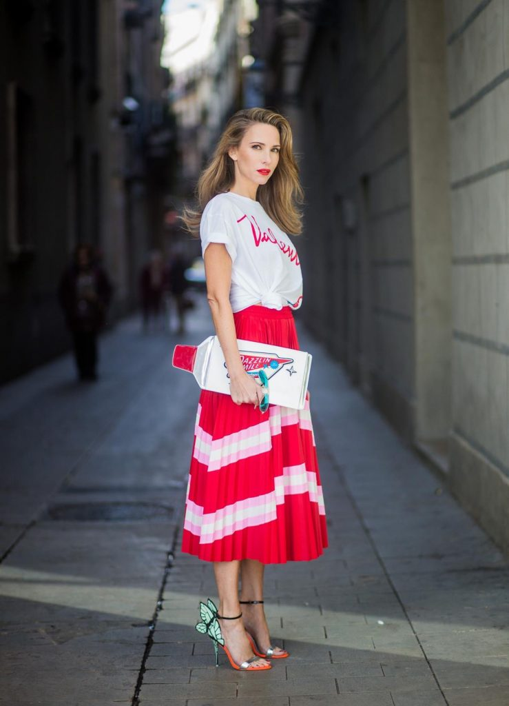 Let us swing - Alexandra Lapp wearing a pleated skirt from Valentino, white t-shirt from Valentino with label print written over the chest with red lipstick, high heel sandals from Sophia Webstar with butterflies on the back, handbag in shape of toothpaste from Yazbukey on November 27, 2017 in Barcelona, Spain.