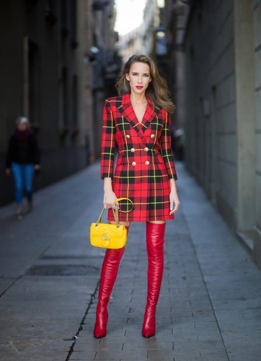 Alexandra Lapp wearing a look all about red, a red checked plaid wool blazer-dress with golden buttons by Balmain, ribbed knit Fendi thigh boots in red Rockoko leather, a yellow Marmont matelasse shoulder bag by Gucci and black Audrey sunglasses by Celine on November 27, 2017 in Barcelona, Spain.