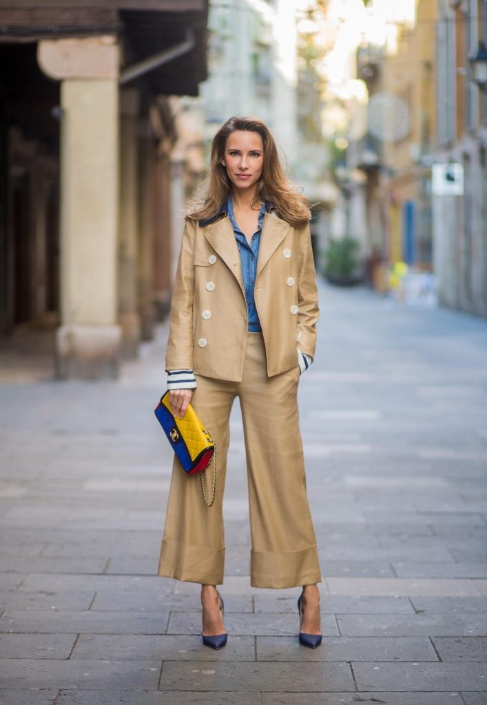 BARCELONA, SPAIN - NOVEMBER 27: Alexandra Lapp wearing wide cut khaki pants from Steffen Schraut, khaki jacket with blue collar and blue and white strips on the bottom of the sleeve from Steffen Schraut, denim shirt by Steffen Schraut, So Kate Pumps from Christian Louboutin in denim, Chanel 2.55 bag in red, blue and yellow with golden logo buckle on November 27, 2017 in Barcelona, Spain.