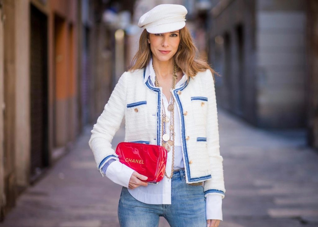 BARCELONA, SPAIN - NOVEMBER 28: Alexandra Lapp wearing a classic navy and white tweed blazer jacket, blue cropped jeans by Steffen Schraut, a white cotton shirt with different shades of blue stripes, denim blue white Louboutin pumps, red Chanel bag, a white cap & vintage gold chains by Chanel on November 28, 2017 in Barcelona, Spain.