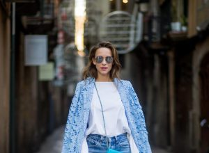 Street Style In Barcelona BARCELONA, SPAIN - NOVEMBER 29: Alexandra Lapp wearing white off-shoulder blouse and light blue lace coat with flowers from Steffen Schraut, silver mirrored sunglasses from Le Specs, multicolored Sophia Webster sandals heels, vintage Levis from ReDone and Chanel purse bag with a long golden strap and Chanel sign in front on November 29, 2017 in Barcelona, Spain.