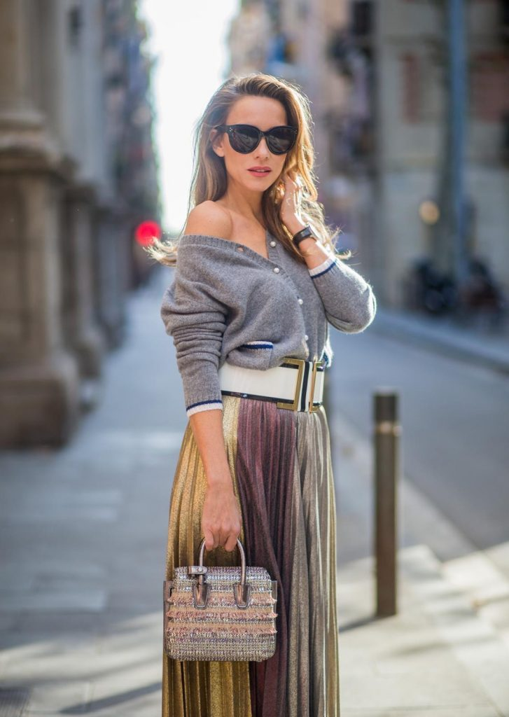 Alexandra Lapp wearing a long pleated metallic skirt with changing gold and red colors, grey cashmere cardigan with pearl buttons and blue and white rims, white and black lacquer waist belt from Balmain with gold buckle and details, Milla handbag in crystal tweed from MCM with metallic yarn and czech crystals, white and green Adidas Stan Smith sneakers and black Celine sunglasses on November 27, 2017 in Barcelona, Spain.