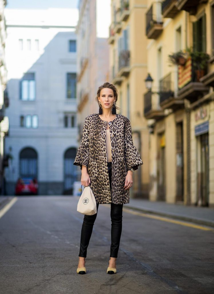BARCELONA, SPAIN - NOVEMBER 29: Take a walk on the wild side, Alexandra Lapp wearing an animal printed jacket with voluminous bell sleeves by Steffen Schraut, a straight cut silk top in light gold, black skinny leather pants from Current Elliott, sand-black Chanel Mules in suede, black Tassel Earrings by Farina for NA-KD and tote bag in beige from Chanel with Chanel logo on November 29, 2017 in Barcelona, Spain.