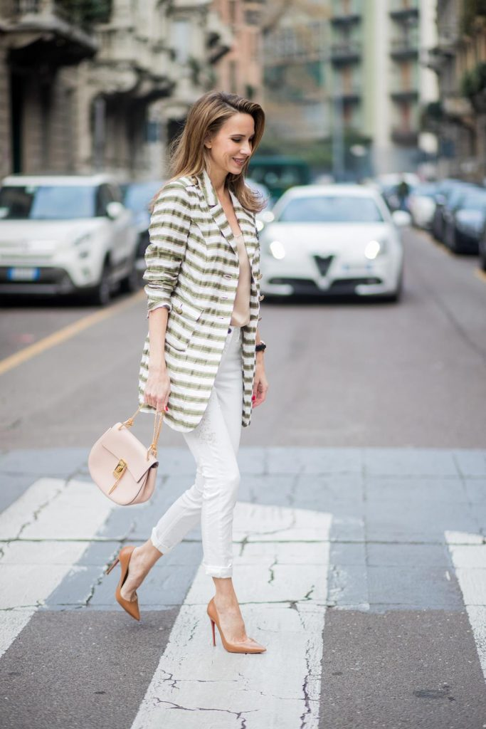Alexandra Lapp wearing a striped blazer in green and white and white pants with gold sprinkles from Airfield, a camel tone satin top by Jadicted, a pastel pink handbag from Chloe with a gold buckle and chain, camel tone pumps by Christian Louboutin and cat-eye shaped sunglasses in black with a gold rim from Maison Mavada seen during Milan Fashion Week Fall/Winter 2018/19 on February 21, 2018 in Milan, Italy.