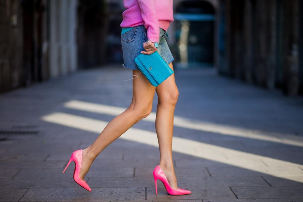 Alexandra Lapp wearing shades of pastels, a mini jeans skirt from Levis, batik cashmere pullover from Heartbreaker in turquoise and pink, Equipment silk blouse in turquoise, little purse bag from Chanel with golden Chanel sign, silver mirrored sunglasses from Le Specs and pink patent So Kate heels from Christian Louboutin on November 28, 2017 in Barcelona, Spain.