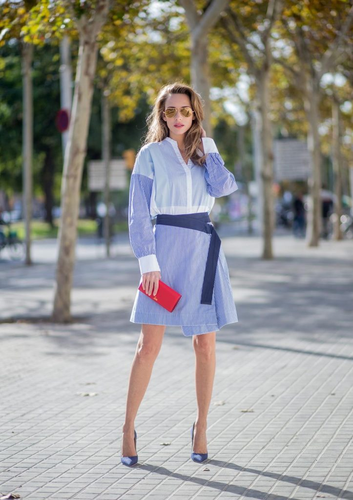 BARCELONA, SPAIN - NOVEMBER 27: Stripe Hype, Alexandra Lapp wearing a multi striped blouse with different stripes from Steffen Schraut, A-line skirt with blue and white stripes with a dark blue waist belt, So Kate pumps from Christian Louboutin in dark blue denim with a pink heel, red Christian Louboutin purse bag with golden chain, Aviator sunglasses in gold on November 27, 2017 in Barcelona, Spain.