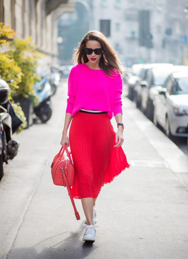 MILAN, ITALY - FEBRUARY 21: Model and Blogger Alexandra Lapp wearing pink and red, a red pleated skirt fro SET, pink cashmere pullover from Jadicted, sneakers from Steffen Schraut, Audrey sunglasses in black from Céline and Boston bag in red from MCM during Milan Fashion Week Fall/Winter 2018/19 on February 21, 2018 in Milan, Italy.