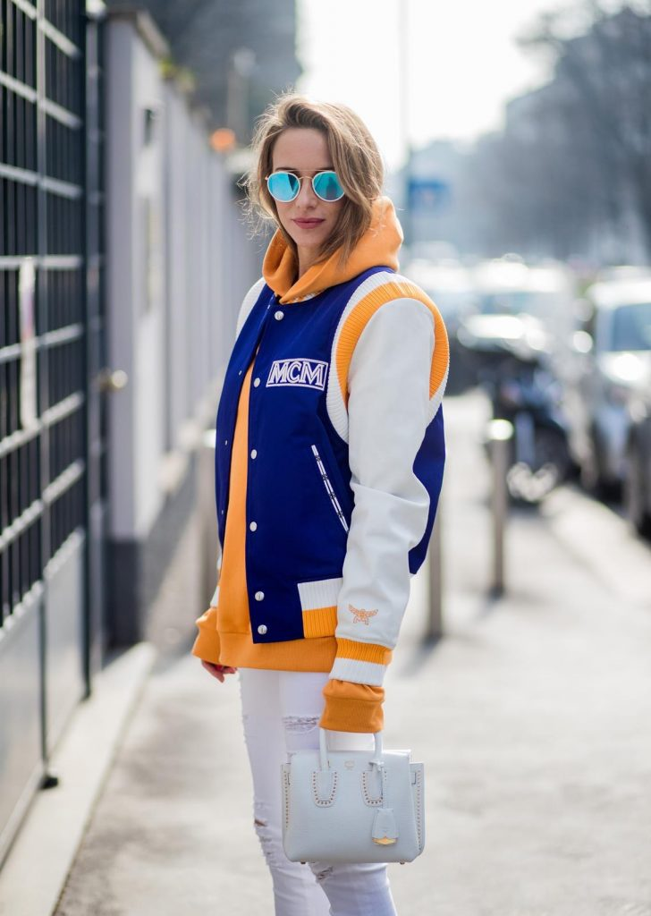 MILAN, ITALY - FEBRUARY 21: Alexandra Lapp wearing college style, a college jacket in blue, white and orange from MCM, an orange hoodie from glam-o-meter, white destroyed jeans from Frame a white Milla handbag from MCM, white pumps from Christian Louboutin and Ray-Ban sunglasses seen during Milan Fashion Week Fall/Winter 2018/19 on February 21, 2018 in Milan, Italy.