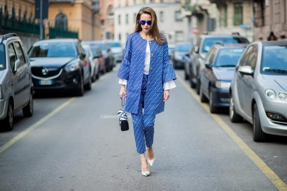 MILAN, ITALY - FEBRUARY 21: Alexandra Lapp wearing dots and stripes, blue trousers with white dots and a matching jacket with a wider short sleeve and a long white blouse from Steffen Schraut, Aigner bag, white pumps from Christian Louboutin seen during Milan Fashion Week Fall/Winter 2018/19 on February 21, 2018 in Milan, Italy.