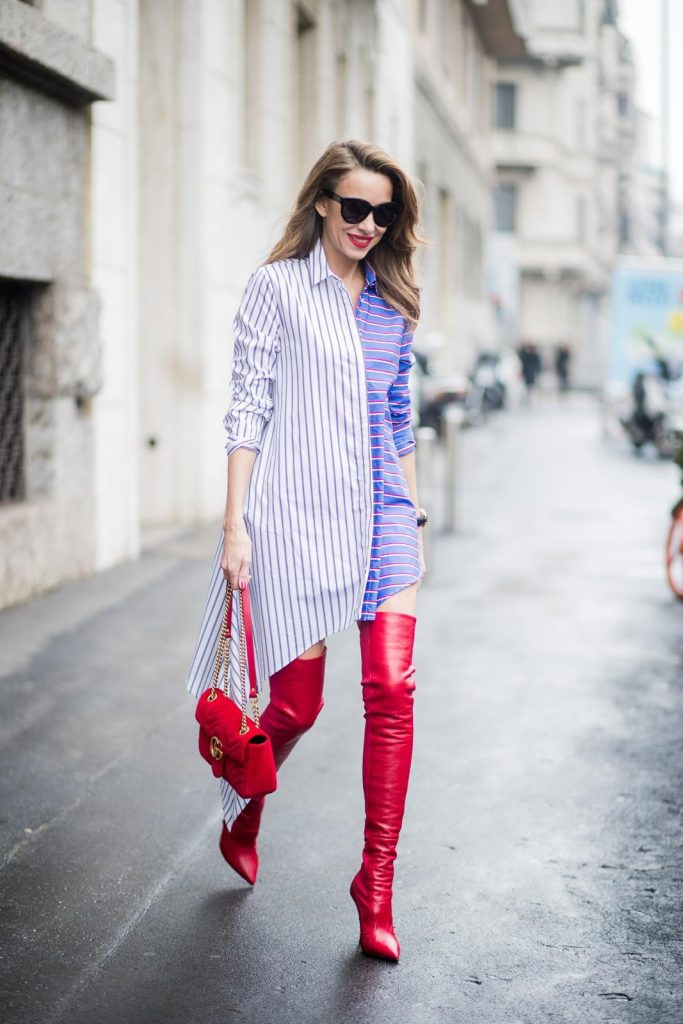 Alexandra Lapp wearing an asymmetric striped blouse by Off-white, red leather over knee boots from Fendi, a red velvet Gucci Marmont handbag with a golden chain and black sunglasses from Celine seen during Milan Fashion Week Fall/Winter 2018/19 on February 24, 2018 in Milan, Italy.