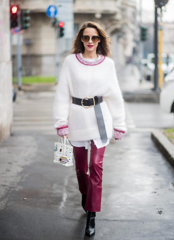Alexandra Lapp wearing flared leather pants in bordeaux by Dorothee Schumacher, an off-white cotton pullover with a bordeaux colored neckline and a long white shirt with a waist line by Dorothee Schumacher, a long black leather belt with a big buckle by Dorothee Schumacher, black leather ankle boots by Gianvito Rossi, cat-eye sunglasses in black with a golden rim by Maison Masada and Anya mini shopper in victory patch from MCM seen during Milan Fashion Week Fall/Winter 2018/19 on February 24, 2018 in Milan, Italy.