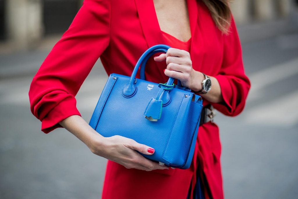 Alexandra Lapp wearing a long red blazer from Zara, a silk top from Jadicted, Collier de chien - a black waist belt with a silver buckle from Hermes, a blue Neo Milla handbag from MCM, a pleated skirt in blue with red stripes from H&M, black boots from Isabel Marant is seen on February 27, 2018 in Paris, France.