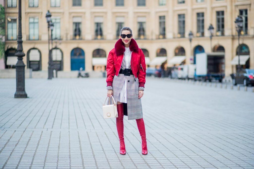 Alexandra Lapp wearing a glencheck coat from Set FAlexandra Lapp wearing a glencheck coat from Set Fashion, red leather over knee boots from Fendi, a white long shirt from Dorothee Schumacher, a black waist belt from Dolce & Gabbana, a red short bomber jacket with a dark red fur collar from Yves Salomon, off white Madame Viv bag from Roger Vivier and black sunglasses from Celine is seen on February 28, 2018 in Paris, France.
