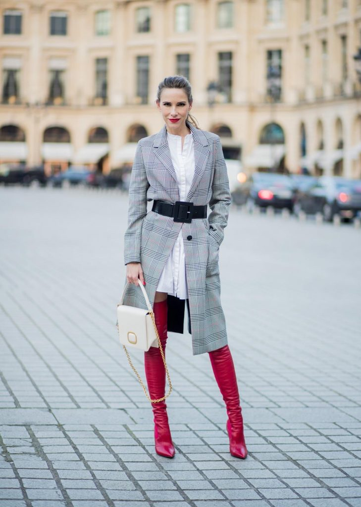 Alexandra Lapp wearing a glencheck coat from Set Fashion, red leather over knee boots from Fendi, a white long shirt from Dorothee Schumacher, a black waist belt from Dolce & Gabbana, a red short bomber jacket with a dark red fur collar from Yves Salomon, off white Madame Viv bag from Roger Vivier and black sunglasses from Celine is seen on February 28, 2018 in Paris, France.