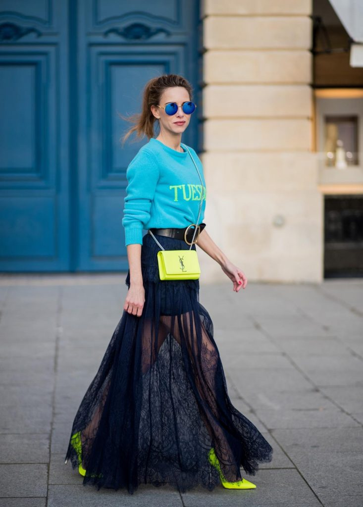 Alexandra Lapp wearing a turquoise pullover with a neon print Tuesday by Alberta Ferretti, a playful dress in black floral lace from Self-Portrait, black waist belt with big buckle from Dorothee Schumacher, blue mirrored sunglasses from Mykita, neon yellow pumps from Christian Louboutin and matching neon yellow handbag from Yves Saint Laurent is seen on February 28, 2018 in Paris, France.