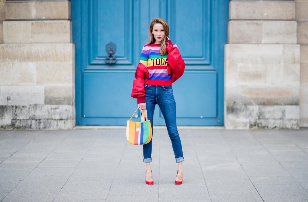 PARIS, FRANCE - FEBRUARY 28: Alexandra Lapp wearing Pullover Alberta Ferretti with today print, AG Jeans denim, Bag MCM Patricia Hobo bag in striped Canvas, Aviator Sunglasses in green from Ray Ban, Heels Gianvito Rossi in patent red, jacket Yves Salomon is seen on February 28, 2018 in Paris, France.