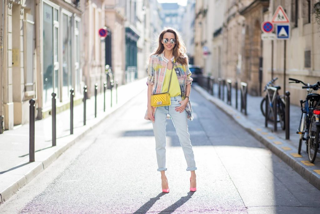 PARIS, FRANCE - MARCH 02: Alexandra Lapp wearing pastel tweed, a long tweed blazer in pastel colors from Airfield, a silk top in bright yellow from Jadicted, light blue boyfriend jeans by Airfield, a neon yellow Chanel bag, neon pink high heels from Christian Louboutin and sunglasses from Le Specs is seen on March 2, 2018 in Paris, France.