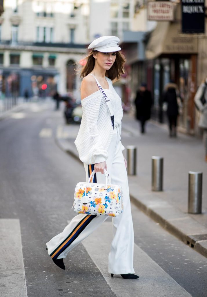 Alexandra Lapp wearing white sport pants with stripes on the side and a white knit v neck pullover from Zara, a white Baker Boy Cap from Chanel, suspenders from Chanel in white with black logo writing, black boots from Isabel Marant and Boston bag in floral print MCM is seen during Paris Fashion Week Womenswear Fall/Winter 2018/2019 on March 4, 2018 in Paris, France.