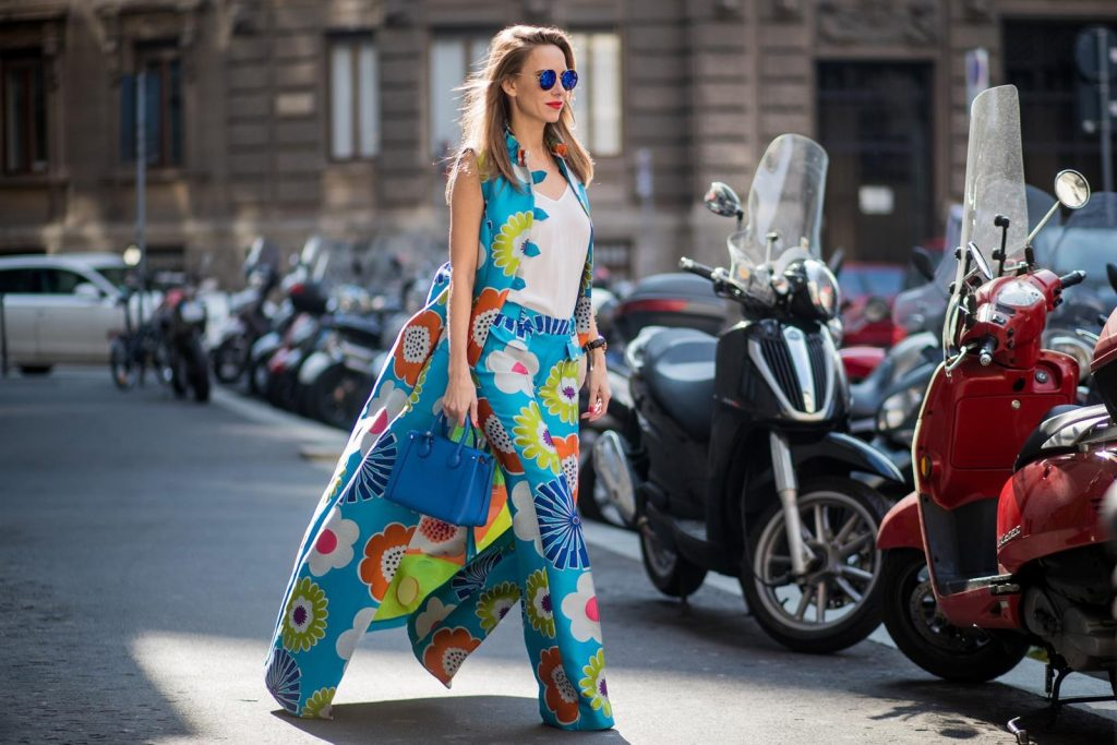 Alexandra Lapp in Seventies Style wearing flower power silk jacquard pants in multicolor with a long leg by Talbot Runhof with matching long vest made of flower power jacquard in multicolor, white silk shirt from Jadicted, blue neo Milla tote bag, Pigalle Follies pumps by Christian Louboutin and blue round sunglasses from Mykita seen during Milan Fashion Week Fall/Winter 2018/19 on February 21, 2018 in Milan, Italy.