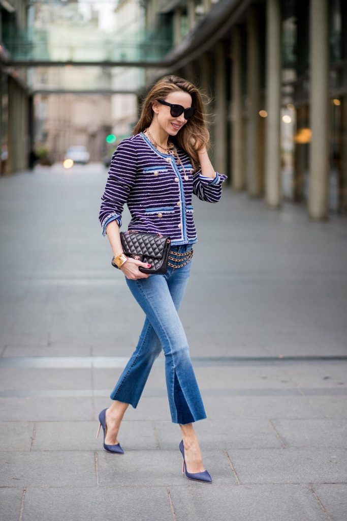 Alexandra Lapp wearing Chanel Vintage: striped tweed jacket in marine tones and flared jeans from Steffen Schraut, a vintage belt with chains and vintage bracelets from Chanel, denim pumps from Christian Louboutin, a 2.55 Chanel handbag in black and black Celine sunglasses is seen on February 27, 2018 in Paris, France.