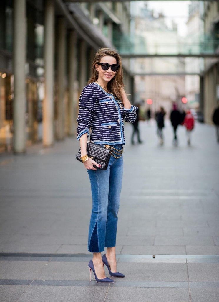 Alexandra Lapp wearing Chanel Vintage: a striped tweed jacket in marine tones and flared jeans from Steffen Schraut, a vintage belt with chains and vintage bracelets from Chanel, denim pumps from Christian Louboutin, a 2.55 Chanel handbag in black and black Celine sunglasses is seen on February 27, 2018 in Paris, France.
