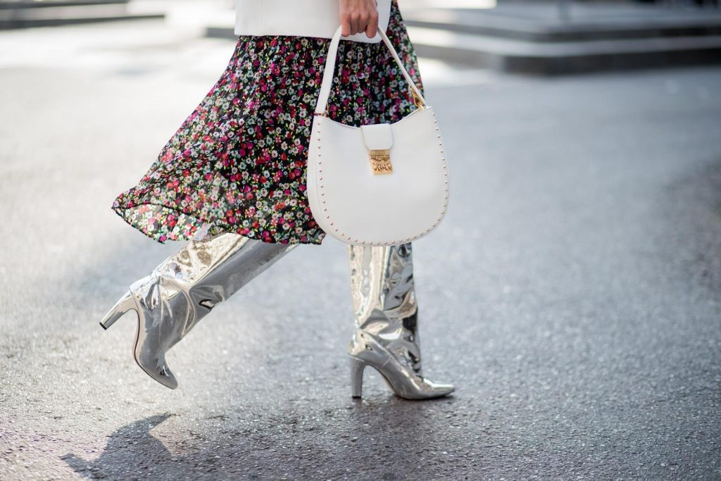 Alexandra Lapp wearing a long flower dress from H&M, silver shiny boots by H&M, a long white blazer from Zara, a lacquer waist belt in white and black from Balmain, a white Patricia Hobo bag with studs and sunglasses from Le Specs in pink seen during Milan Fashion Week Fall/Winter 2018/19 on February 21, 2018 in Milan, Italy.