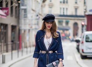 Alexandra Lapp wearing silver stitches: dark blue cropped pants and blazer shaped cardigan from Airfield, So Kate heels in patent black Christian Loubboutin, white silk top from Jadicted, bakerboy cap and pearl necklace from Chanel, Collier de Chien belt and clutch in black from Hermes, IWC watch is seen during Paris Fashion Week Womenswear Fall/Winter 2018/2019 on March 3, 2018 in Paris, France.