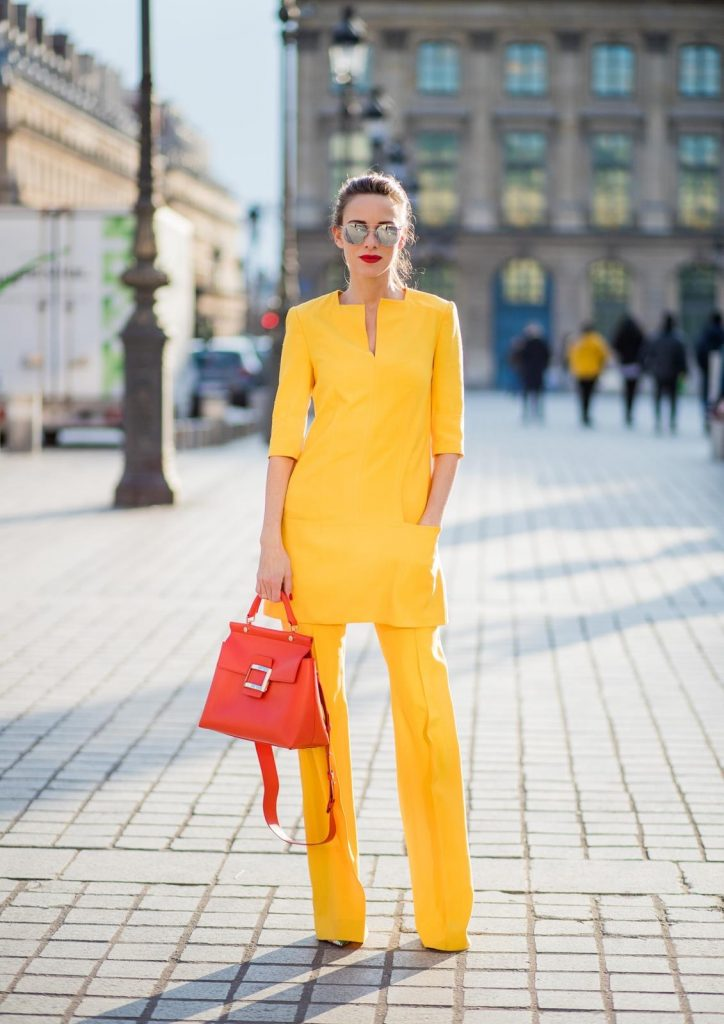 Alexandra Lapp wearing taroni silk pants & a tunic in yellow from Talbot & Runhof, small Viv Cabas in orange with shoulder strap, mirrored sunglasses from Le Specs and Christian Louboutin So Kate Pumps is seen on February 28, 2018 in Paris, France.