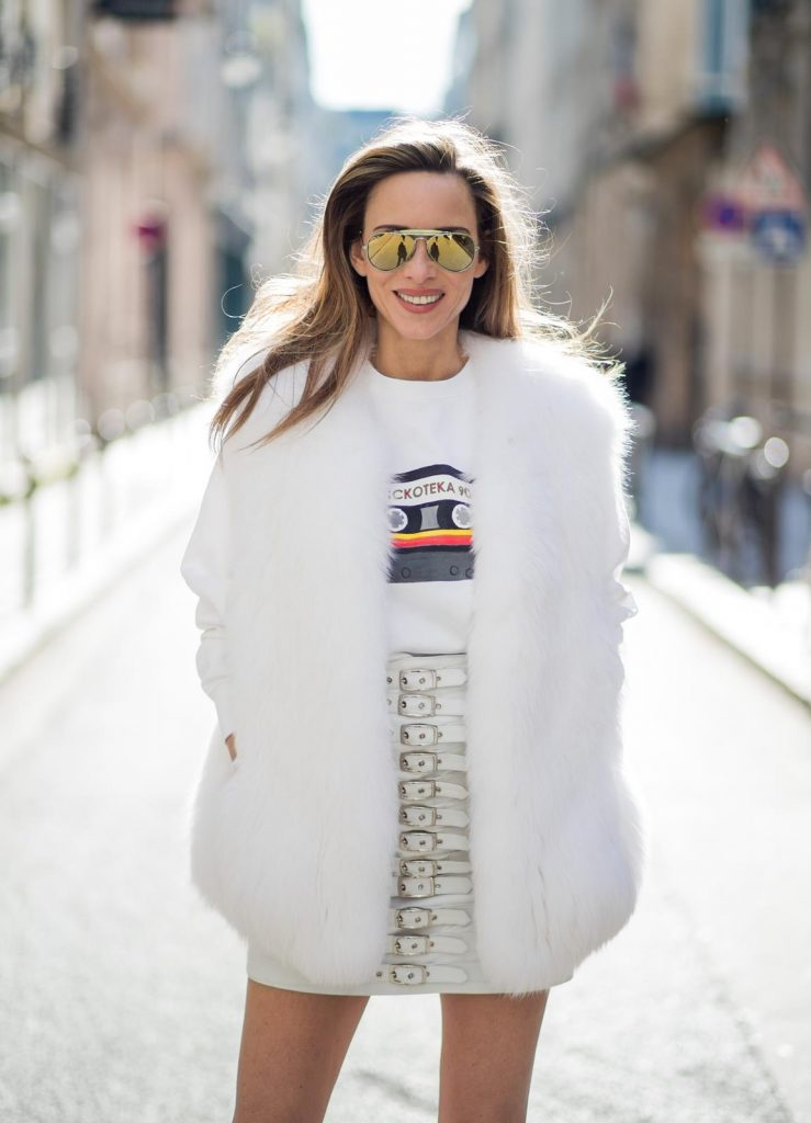 Alexandra Lapp in Think White: she is seen wearing a white leather miniskirt from Manokhi, Selfmade Sweater from Wodka Ogurez, Yves Salomon fur veste in white, Aldo heels with red lips, vintage Ray-ban in yellow and a boy bag from Chanel in gold during Paris Fashion Week Womenswear Fall/Winter 2018/2019 on March 5, 2018 in Paris, France.